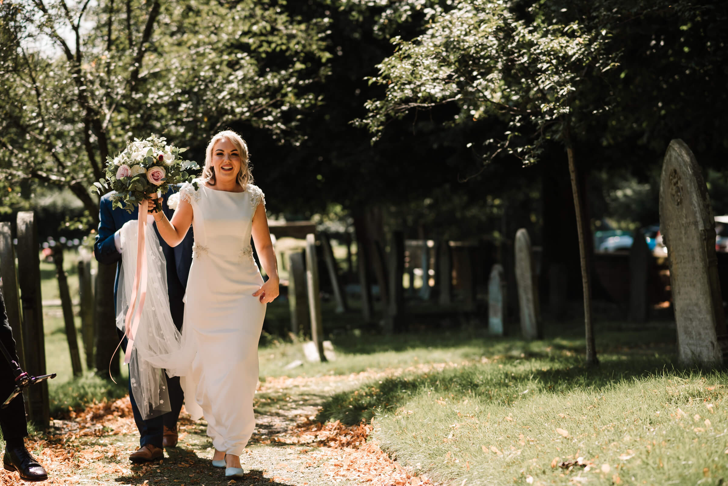 bride walking up church path holding bouquet