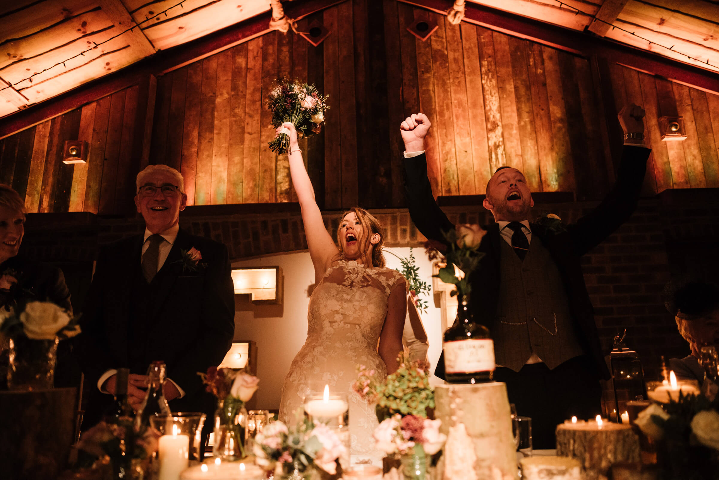 bride and groom cheering at top table