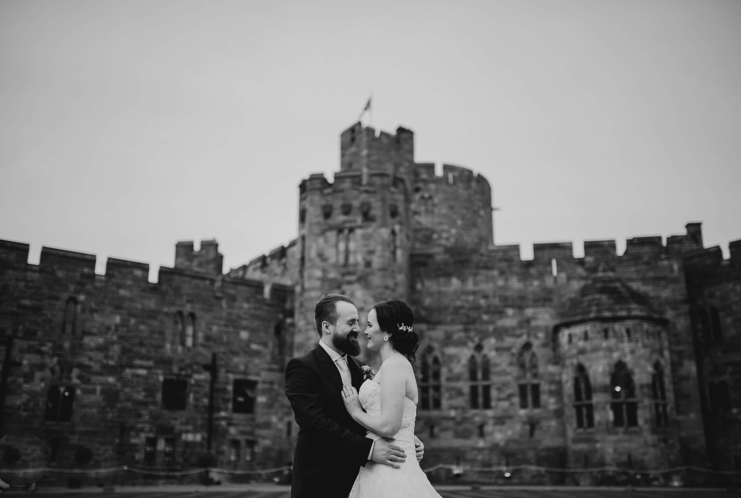 bride and groom close together with castle in back ground