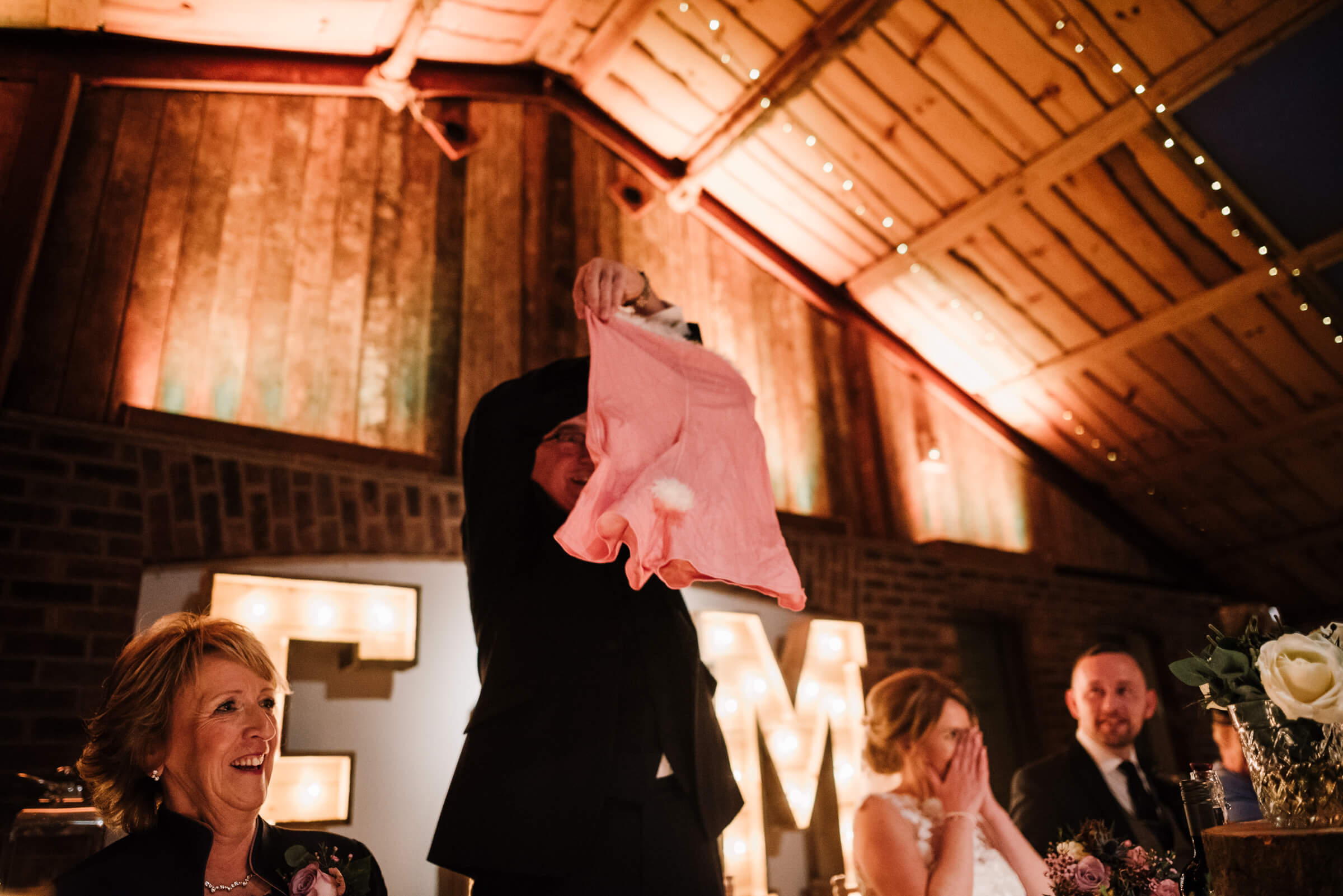 father of bride holding up large pink underwear