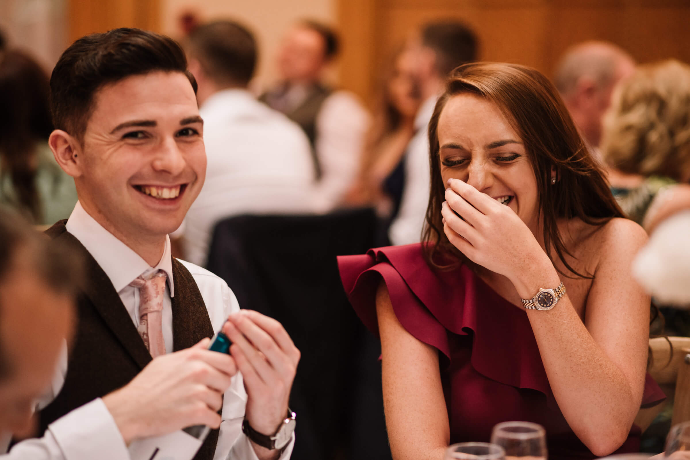 two guests laughing during speeches