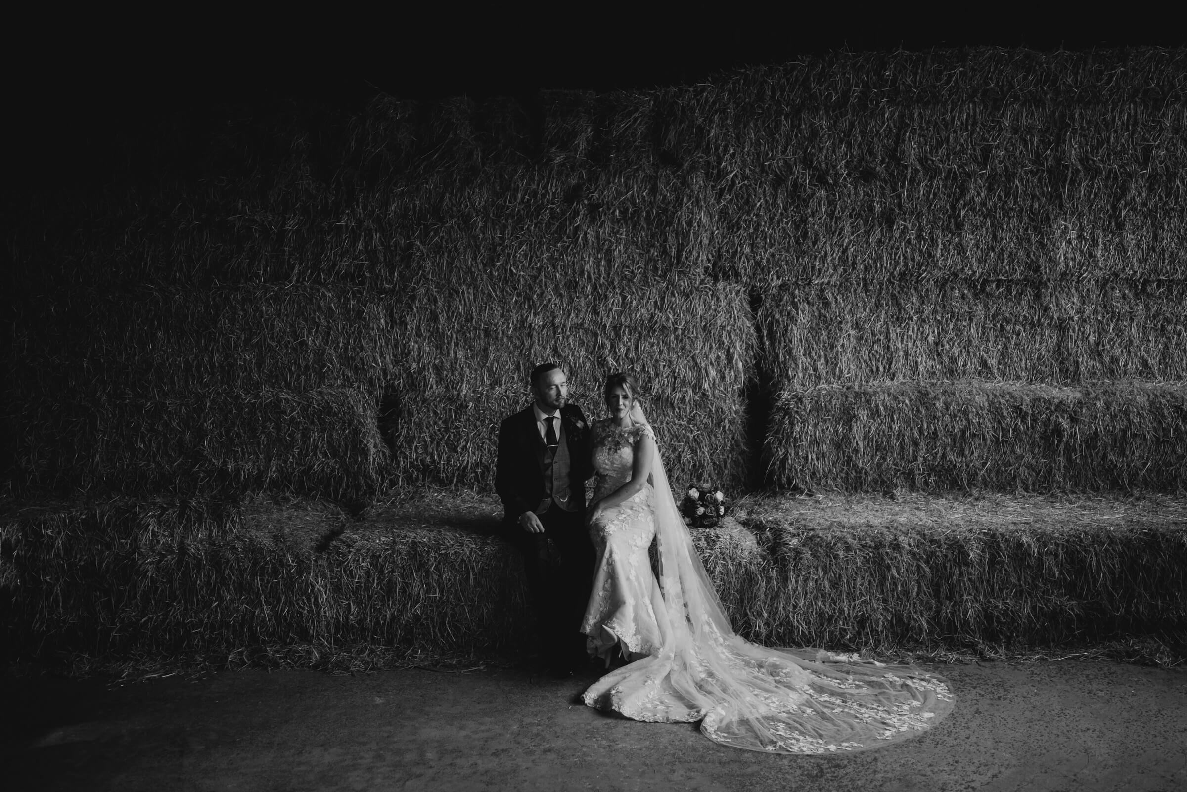 bride and groom portrait on hay bales