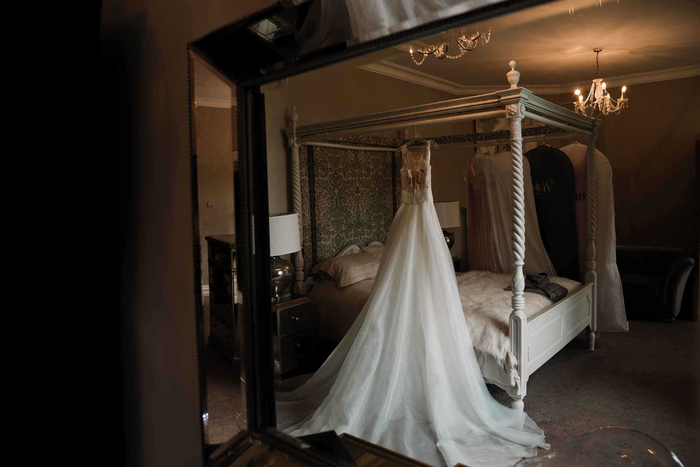wedding photography of wedding dress hanging from four poster bed