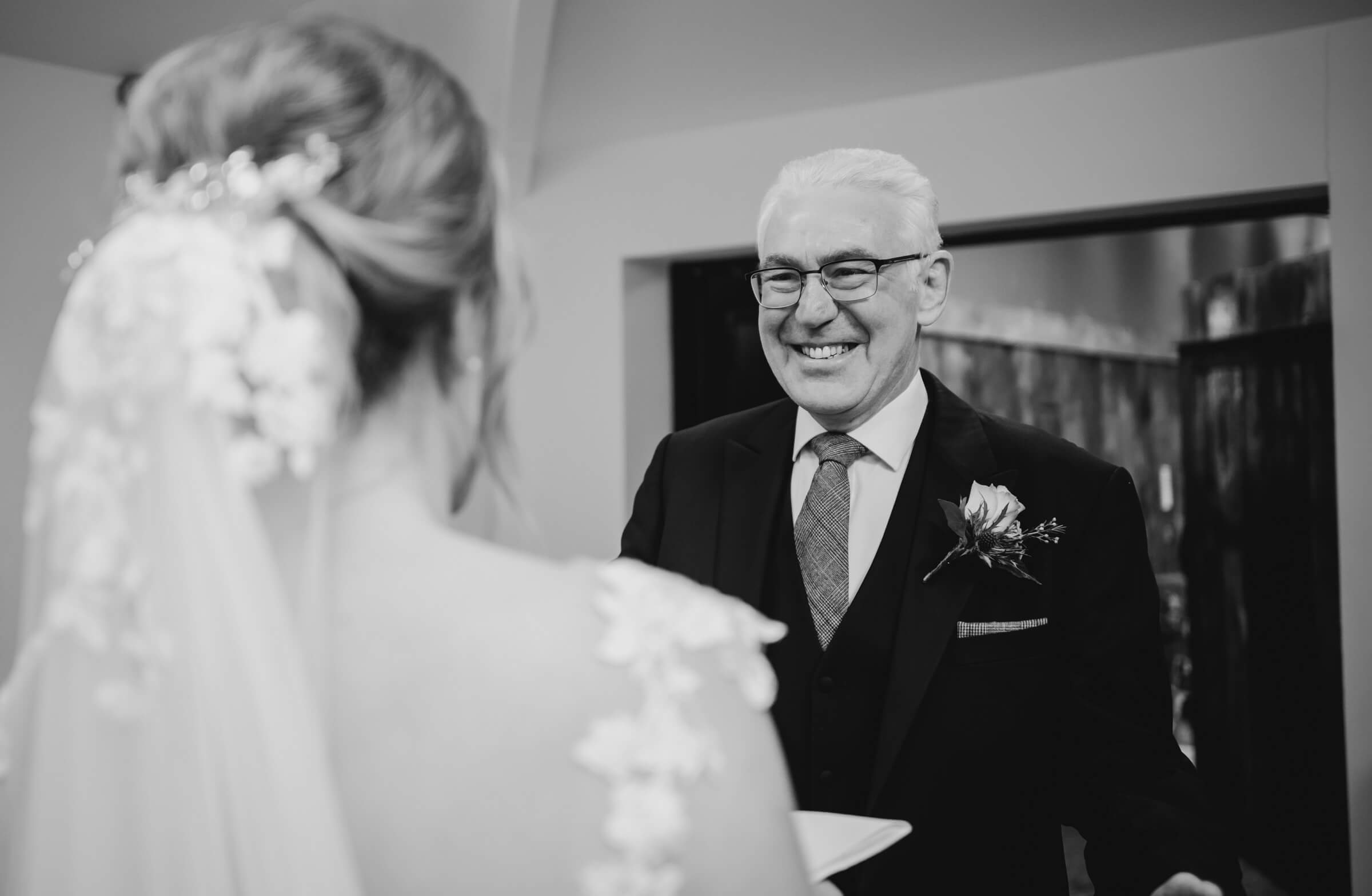 father smiling at bride