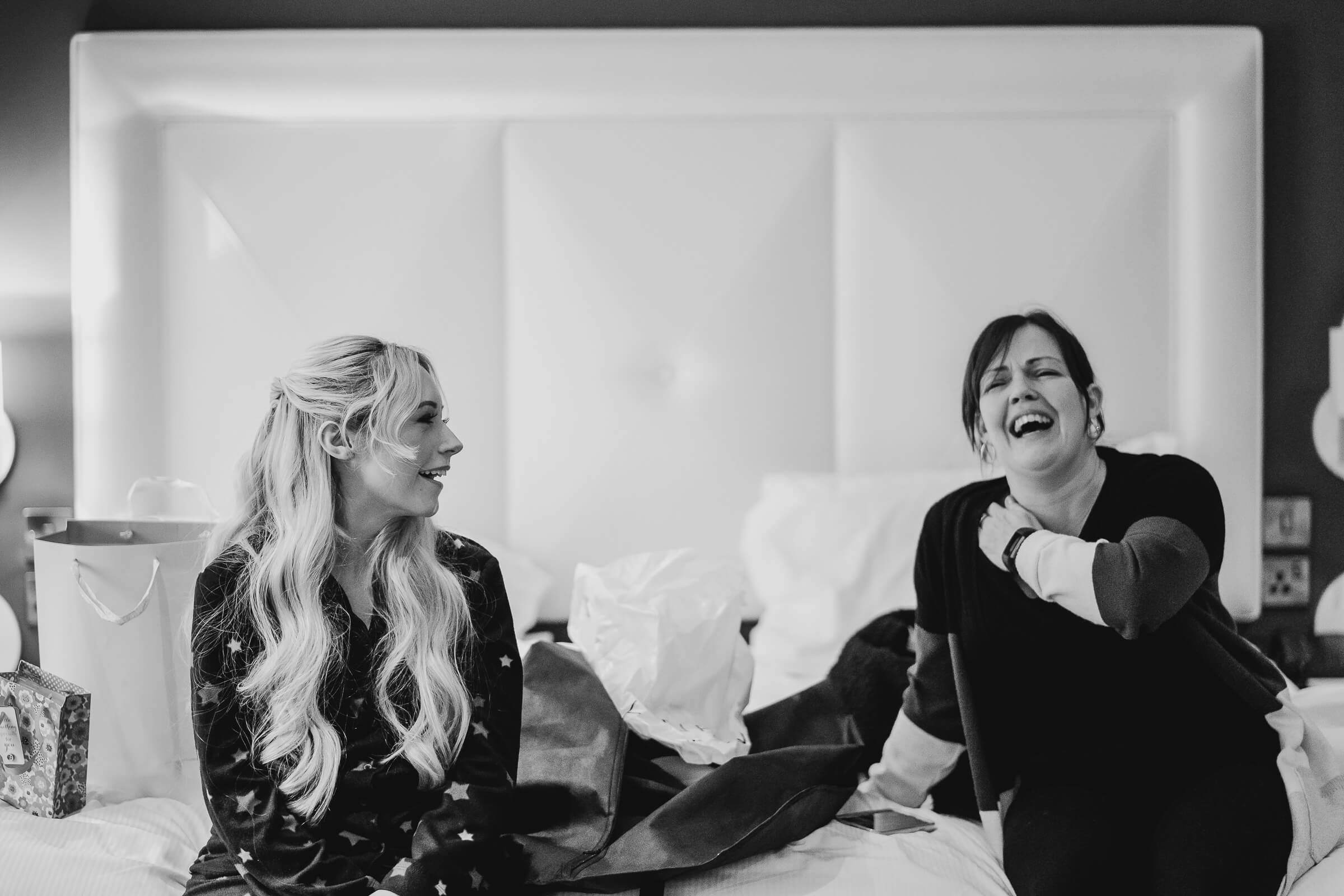 Bridesmaids laughing on bed