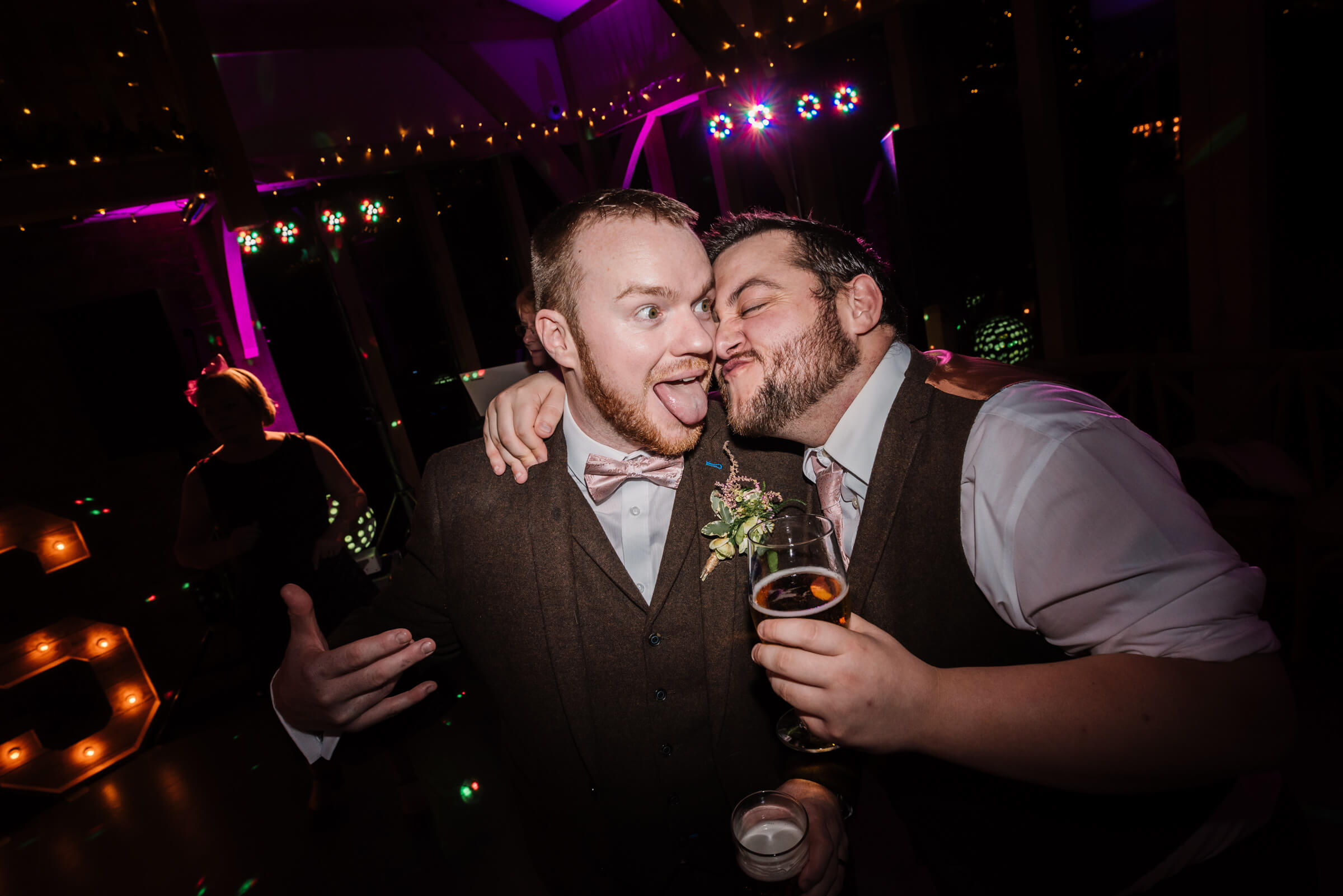groom pulling funny face with groomsman