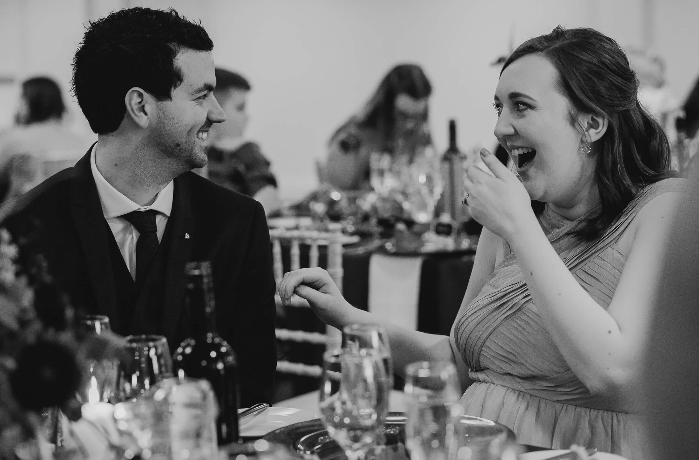 Bridesmaid and partner laughing