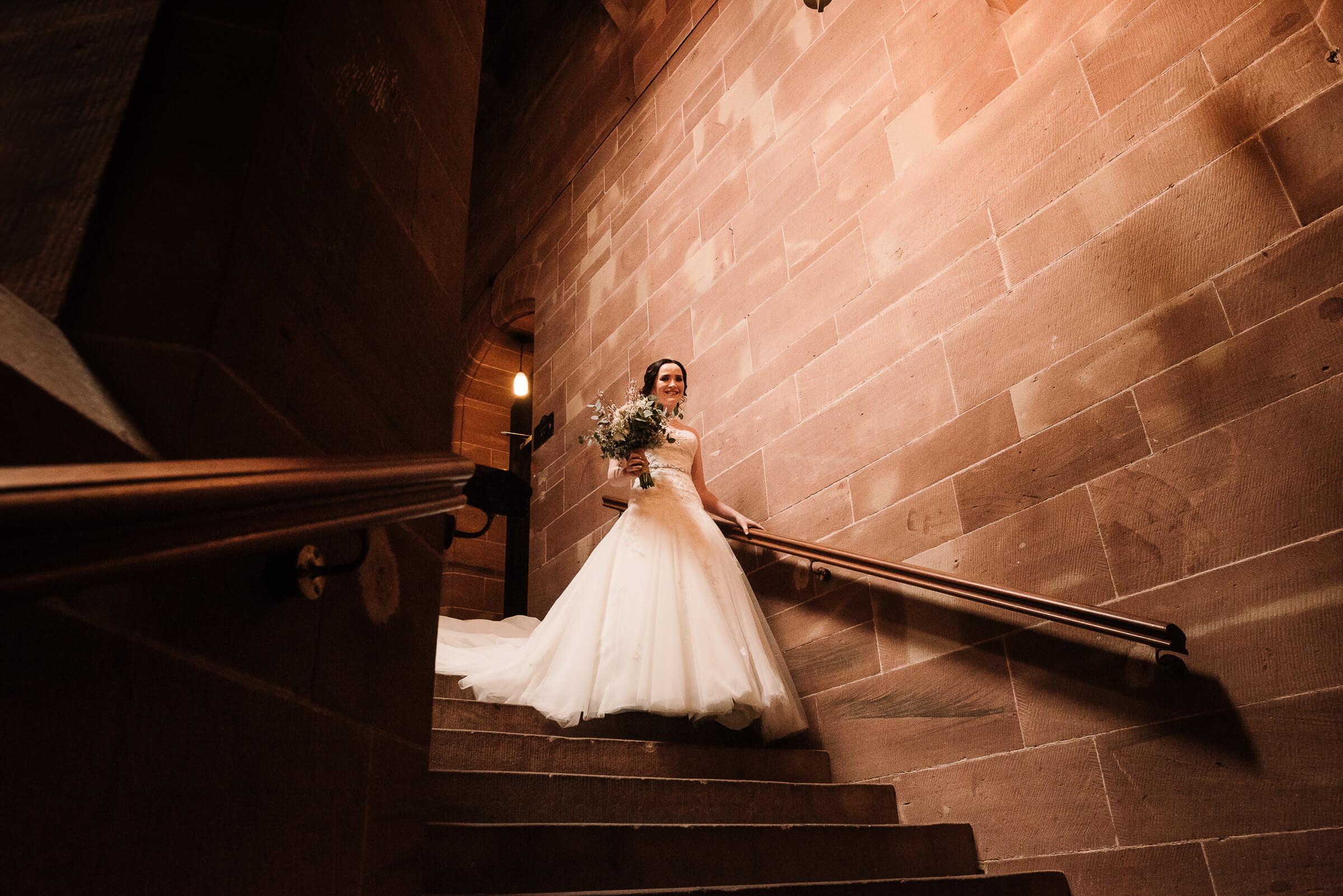 bride walking down stone staircase