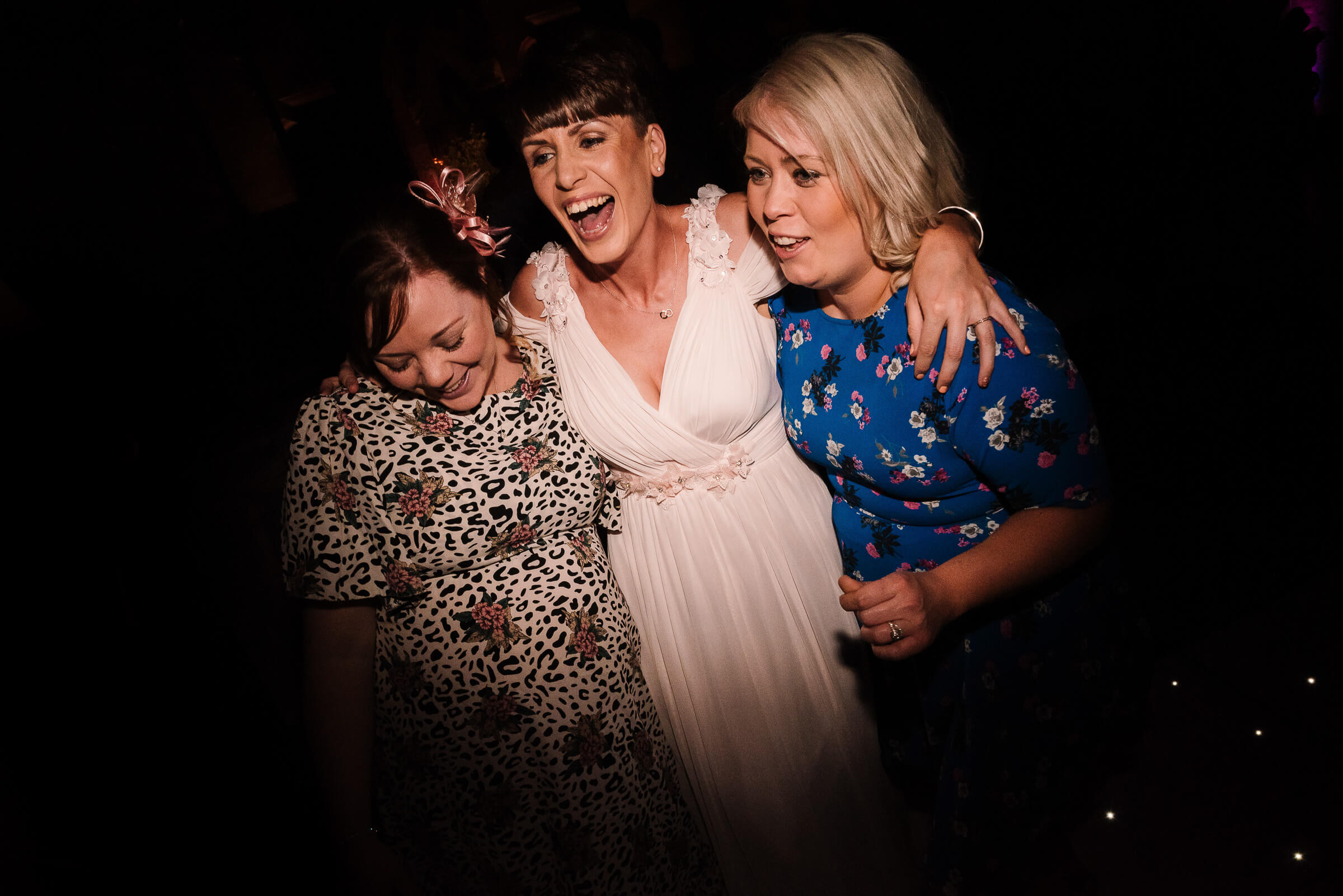 brides sister smiling with friends on dancefloor