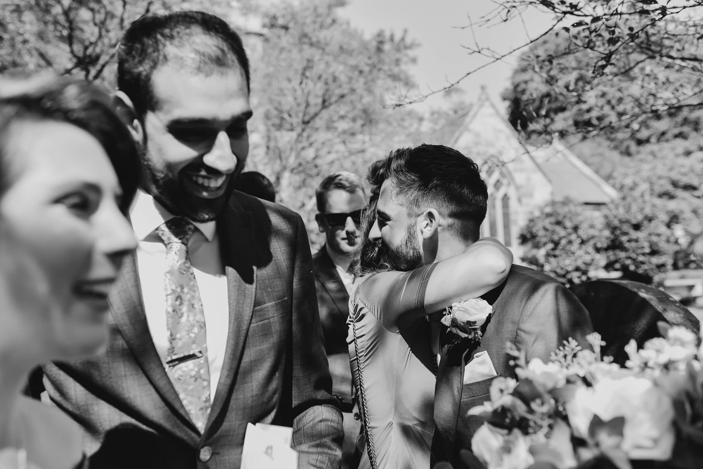 groom hugging guests as they leave church