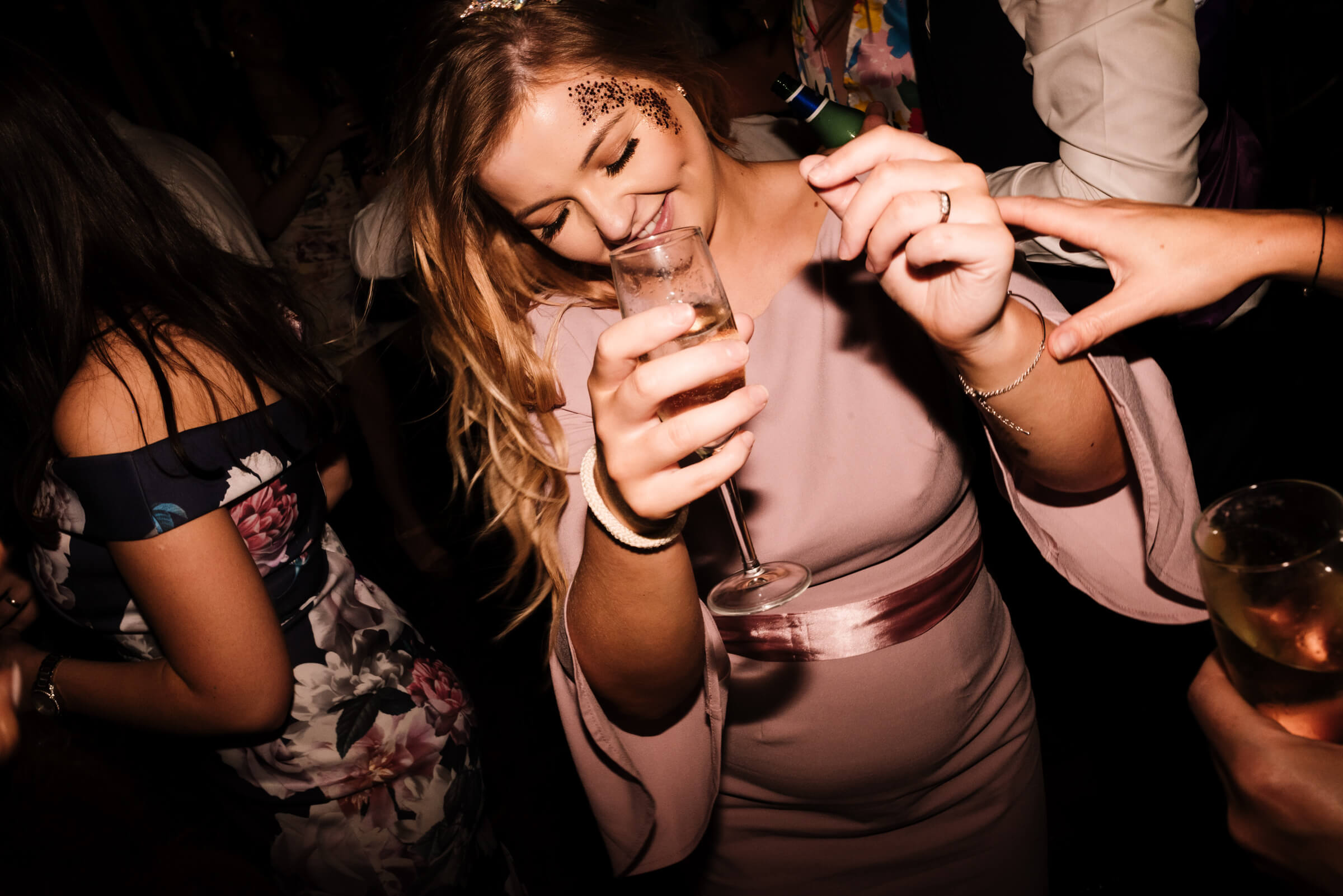 girl holding glass of champagne and dancing
