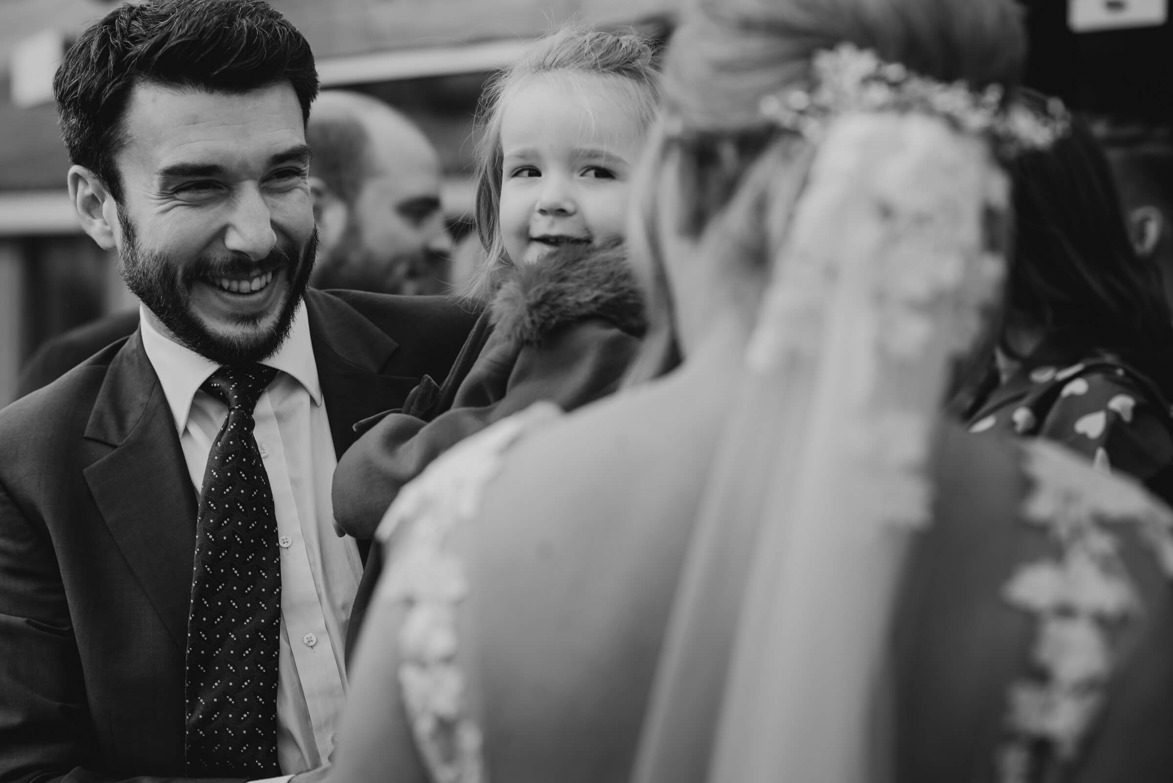 father with his little boy smiling at bride