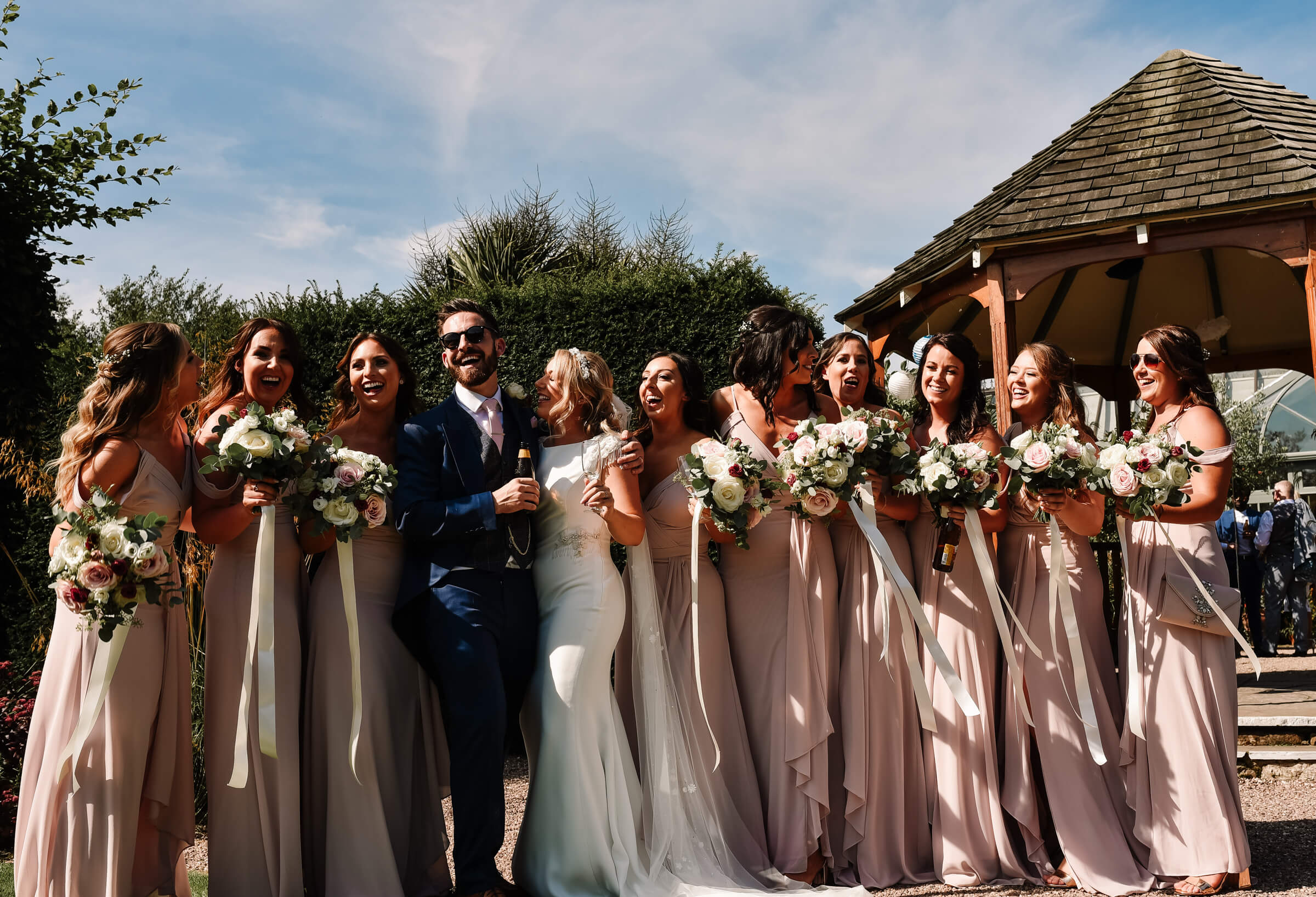 groom smiling with bride and bridesmaids