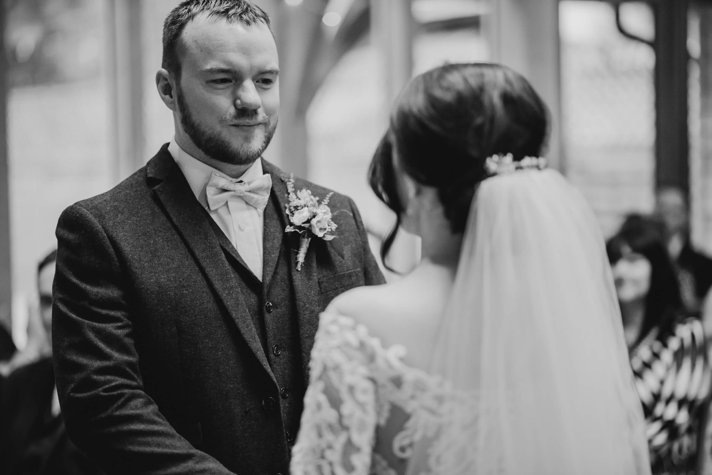 groom smiling at bride during vows
