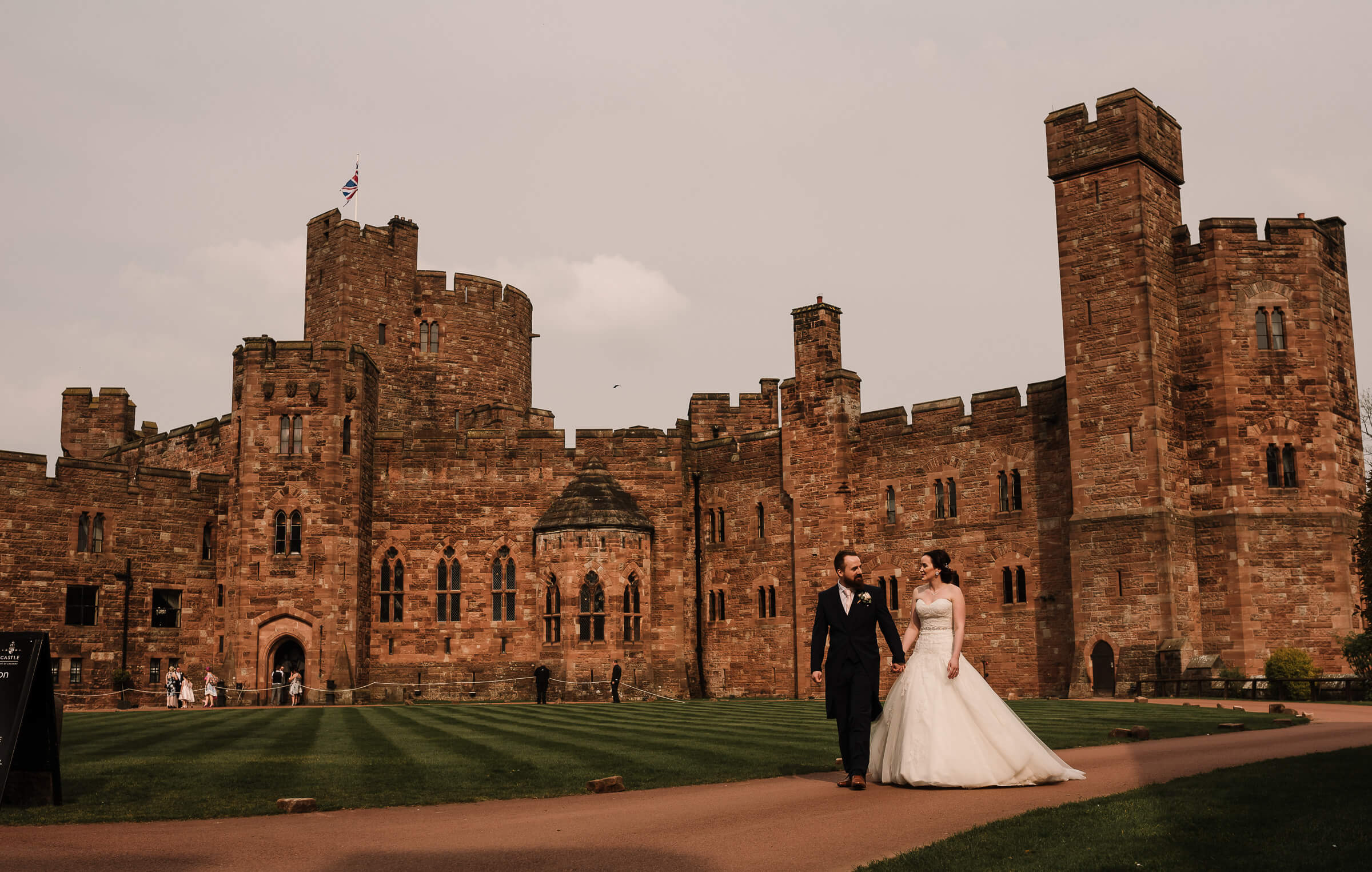 bride and groom strolling outside castle