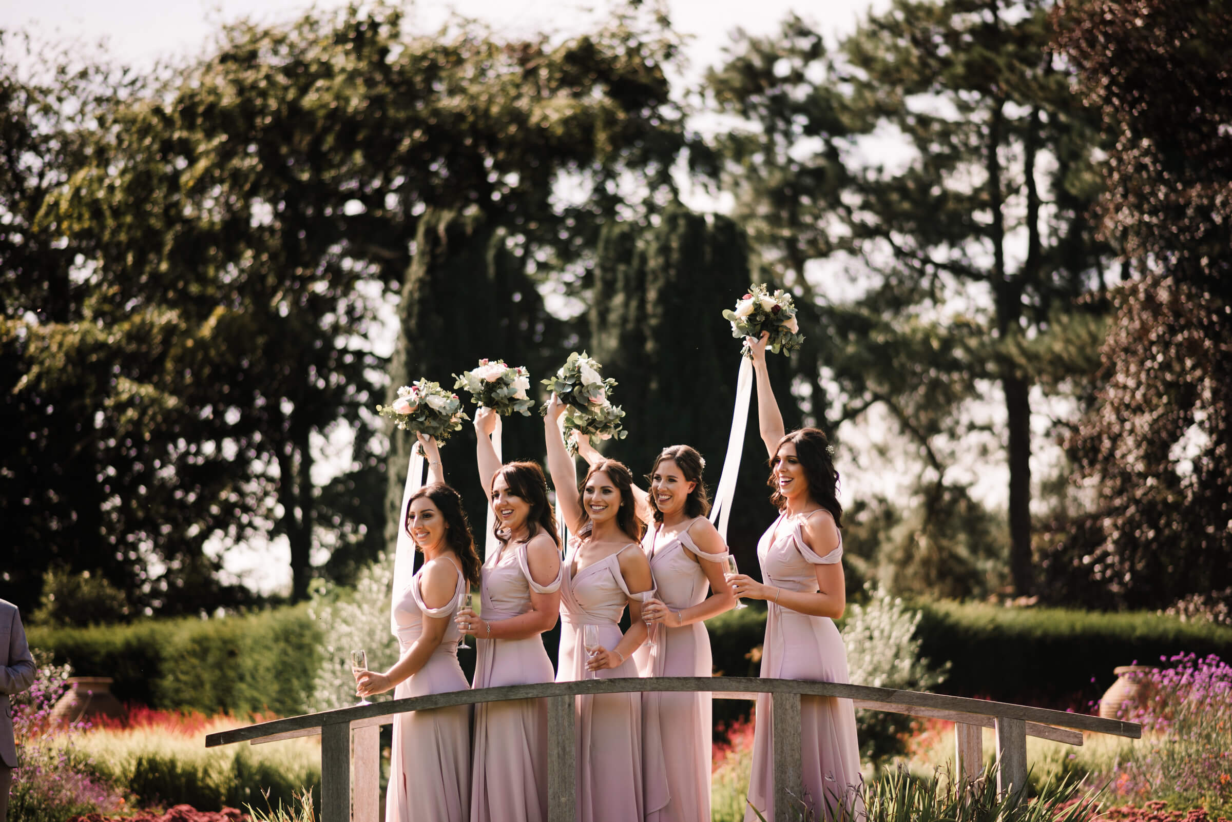 bridesmaids holding bouquets in air