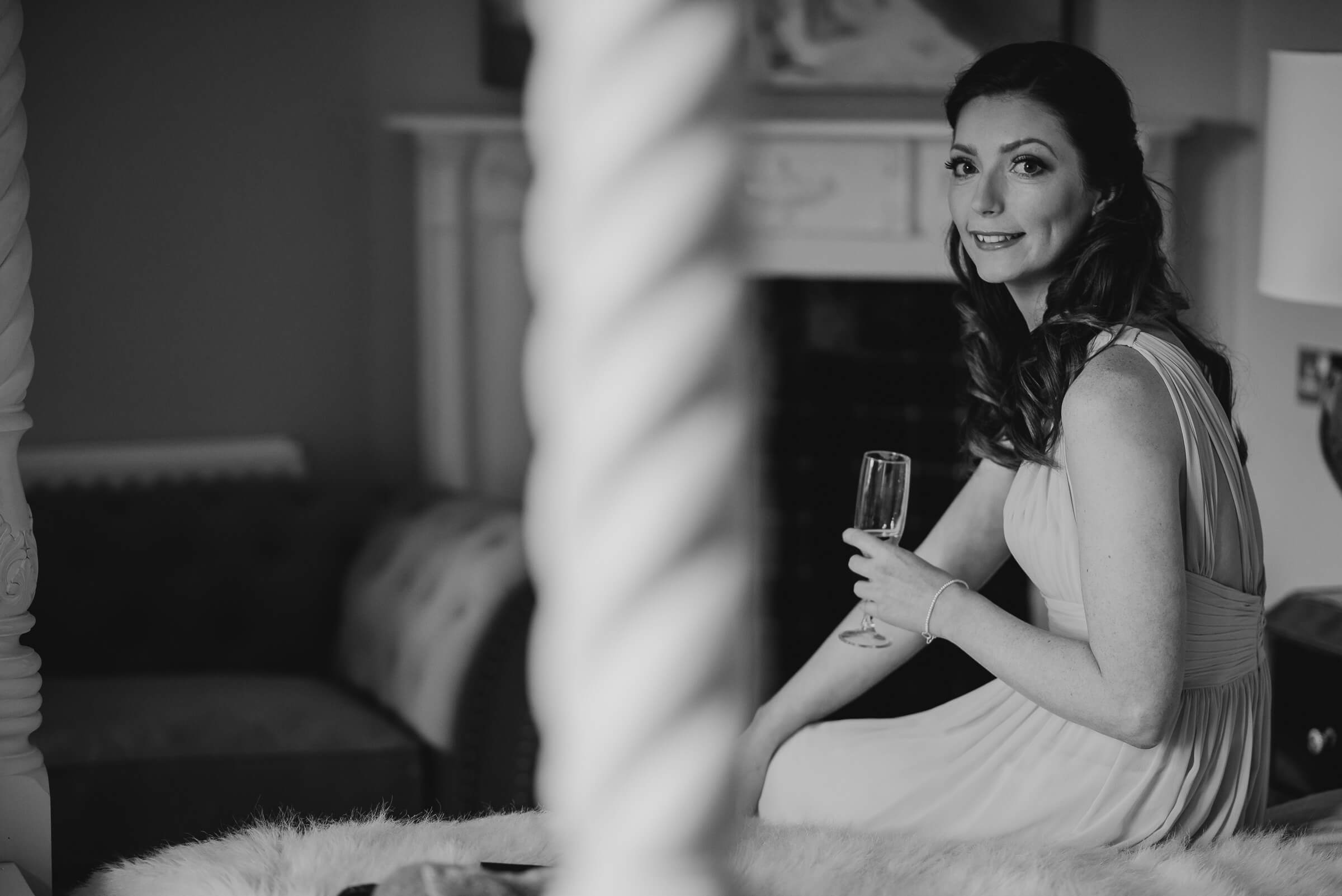 black and white wedding photo of bridesmaid sat on bed