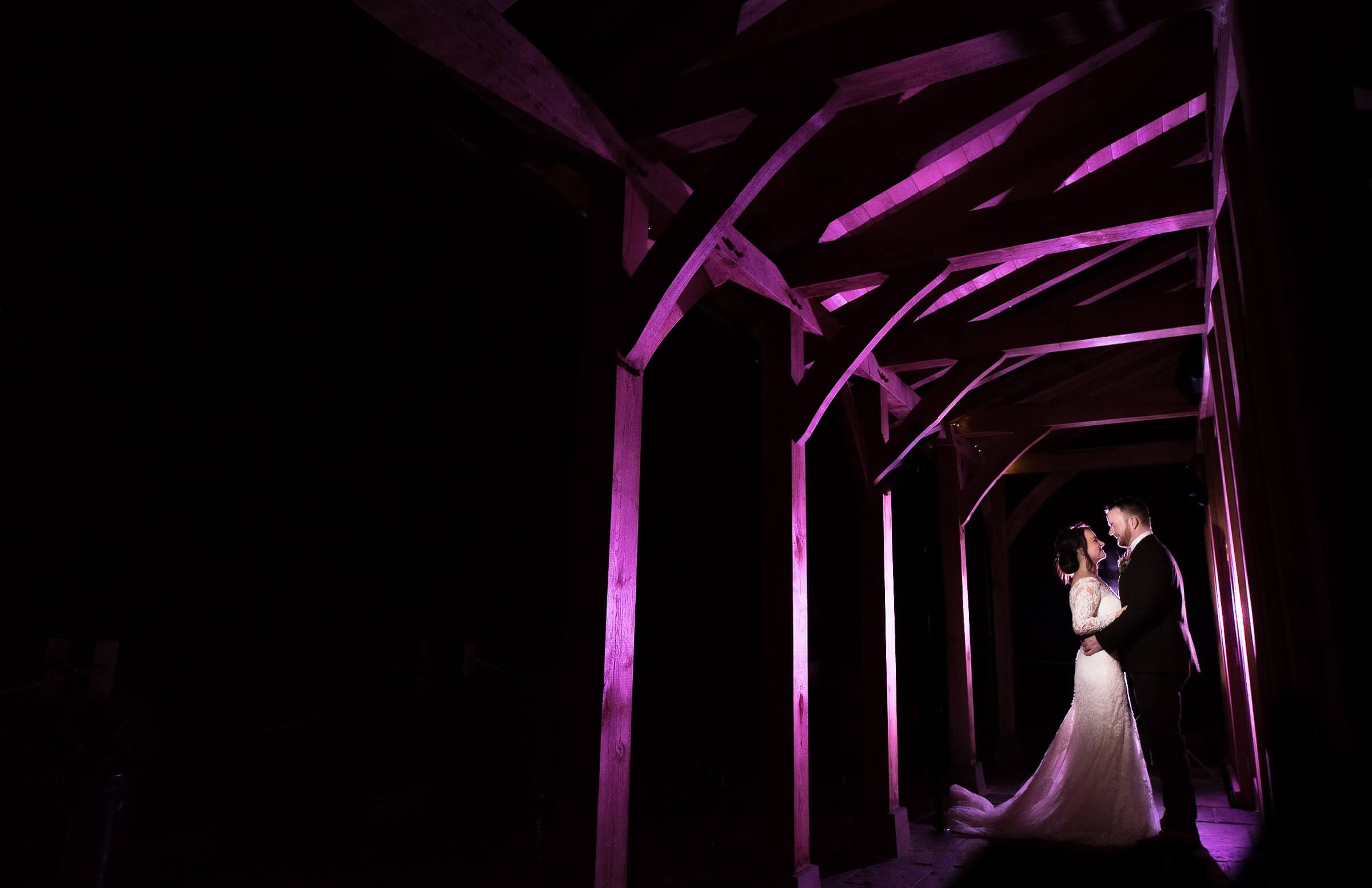 creative image of bride and groom under wooden beams