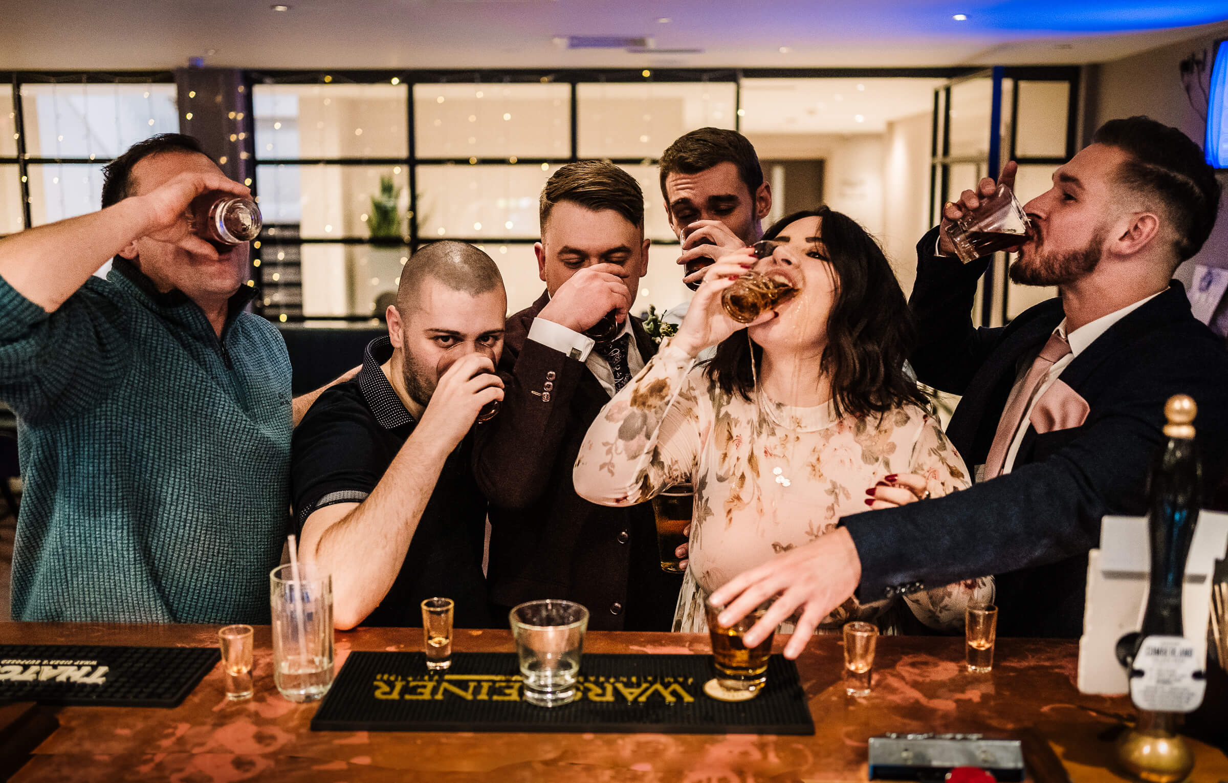 Groom and guests having shots in bar