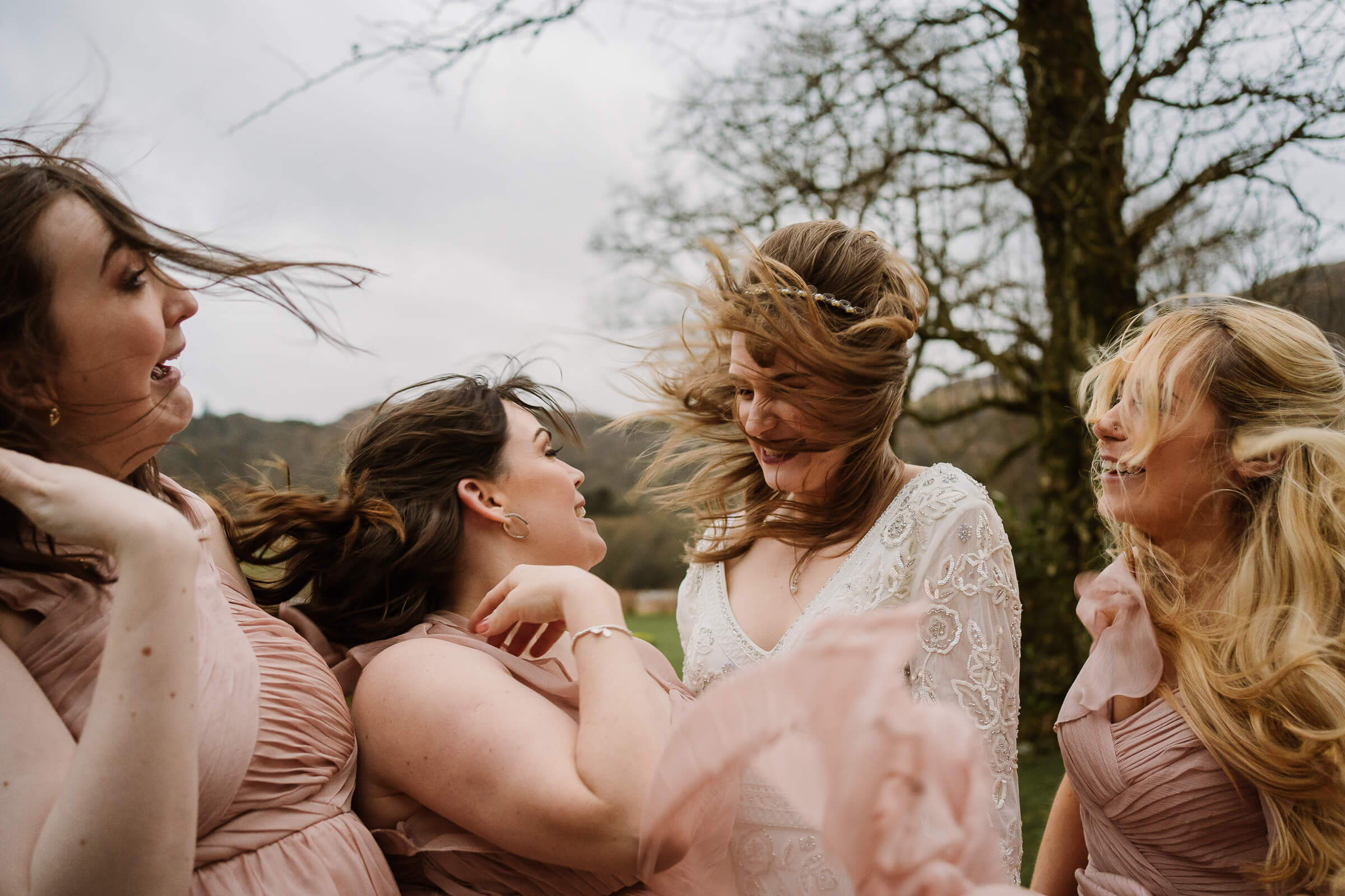 Bride and bridesmaids getting blown by wind