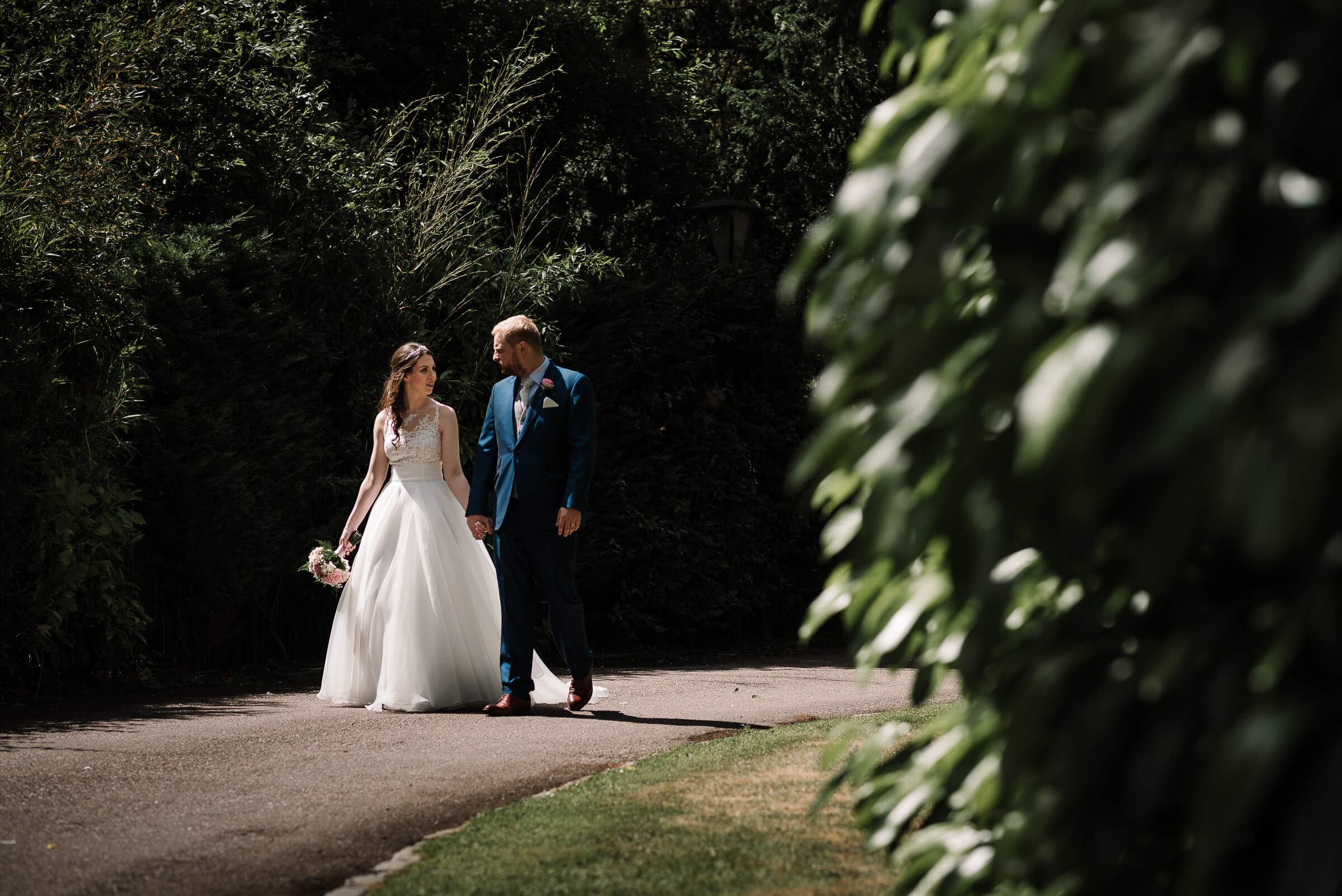 bride and groom walking along driveway