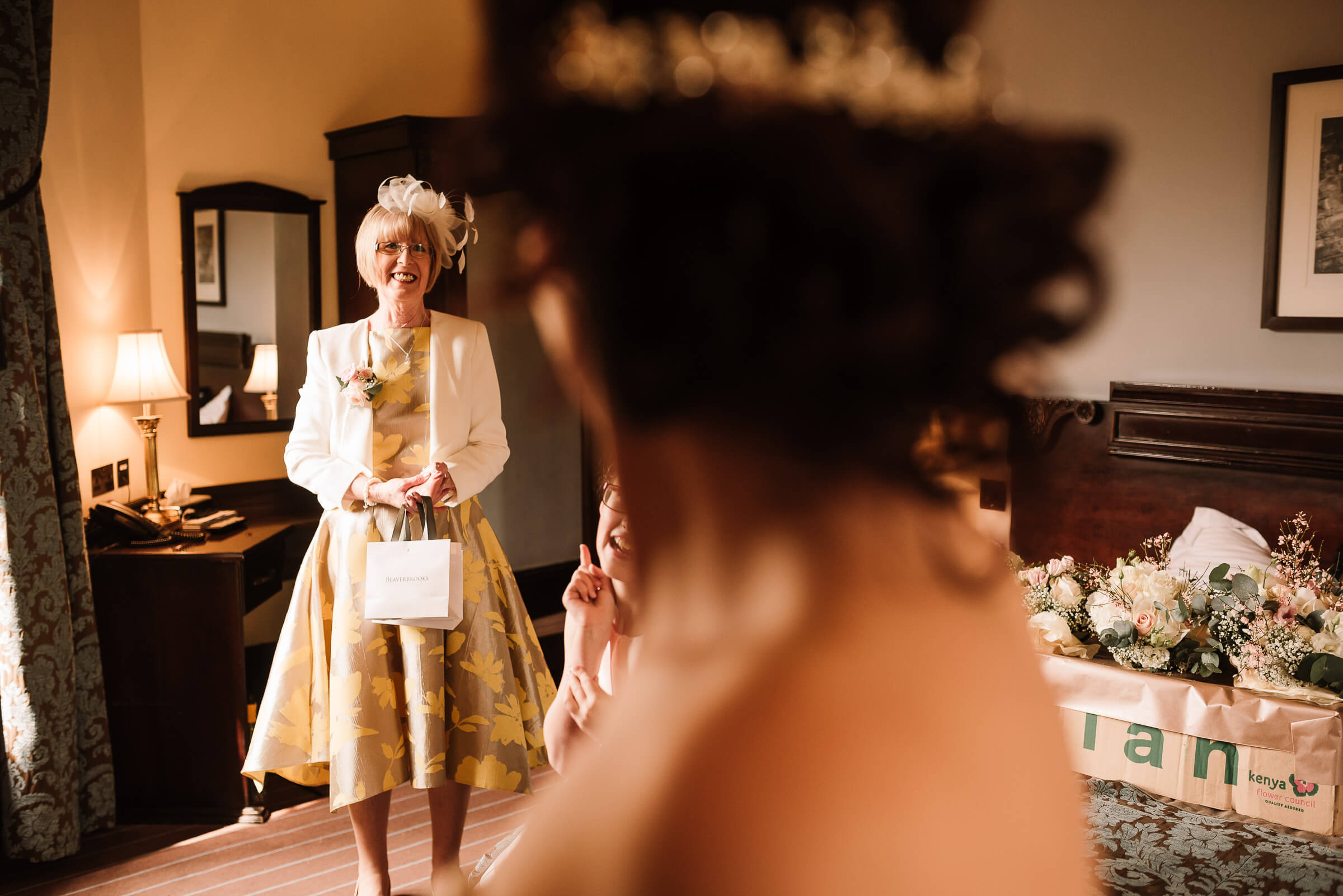mother of the bride smiling at bride in her dress