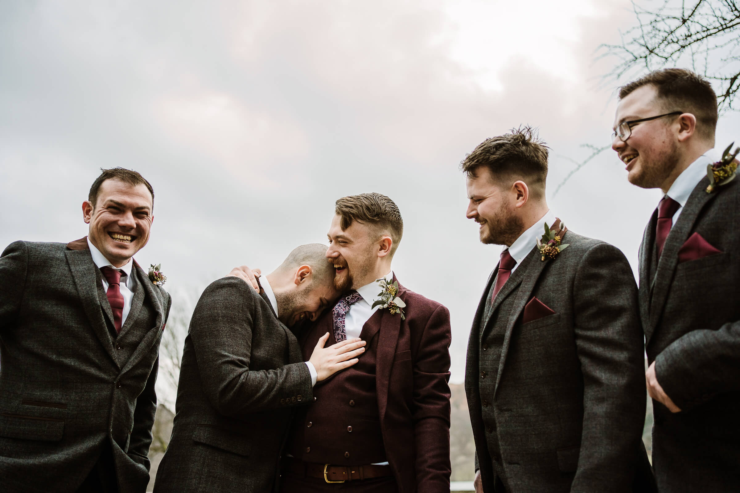 Groom hugging friends with groomsmen