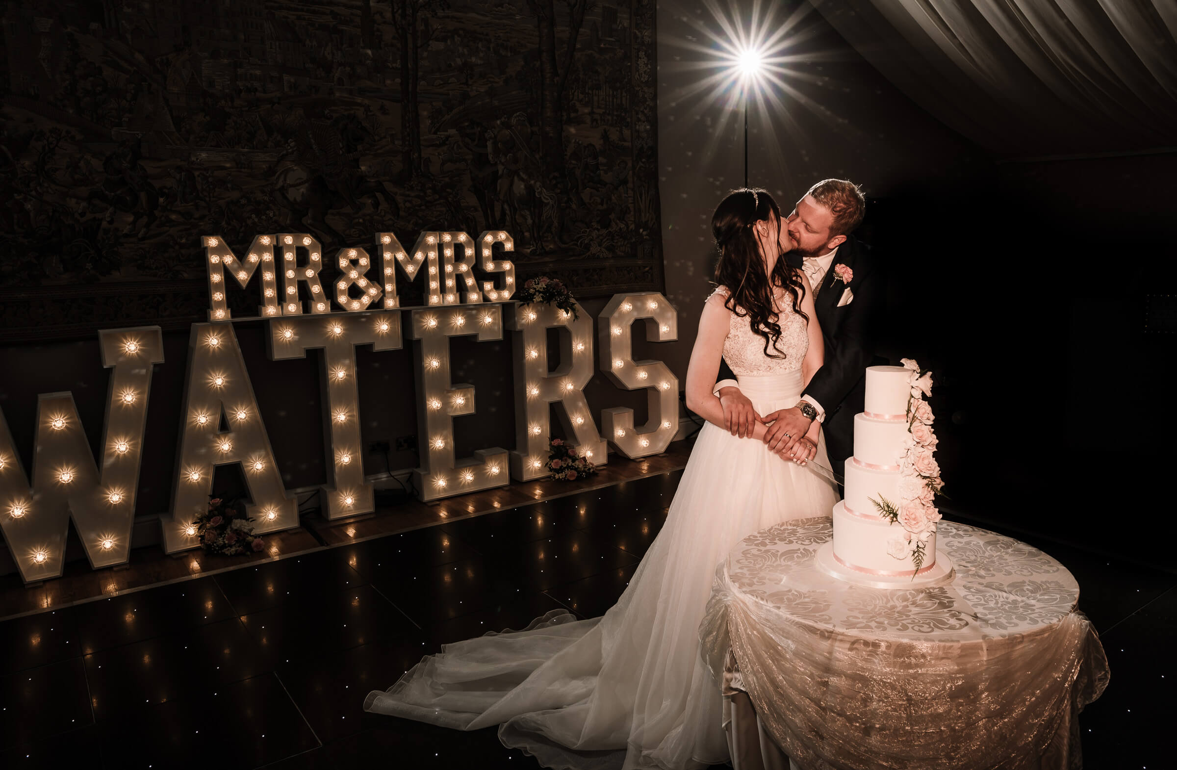 bride and groom kissing by light up letters