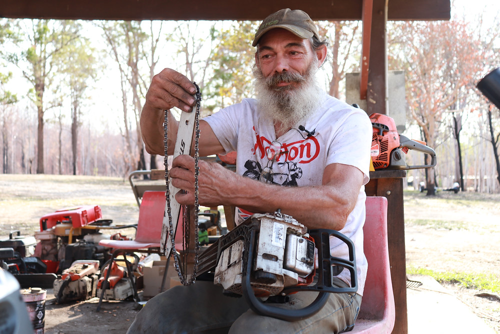 Man fixing chainsaw after bushfire Nymboida Australia (Grace and Hugh Piano Songwriter Blog)