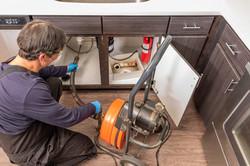 plumber unclogging a kitchen sink