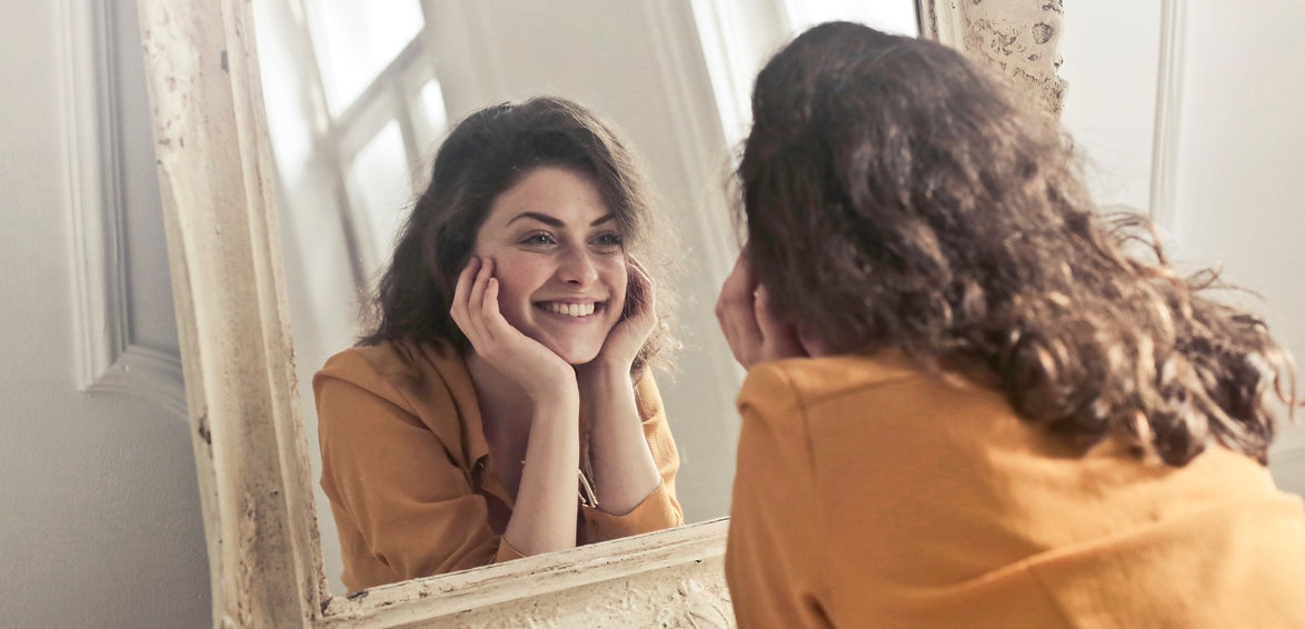 Woman looking in a mirror with head in hands smiling