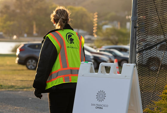 A person wearing a neon parking vest looks out over a parking lot