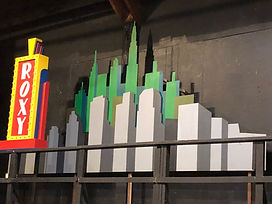 A set piece that has a Roxy sign on the left and a city scene on the right.