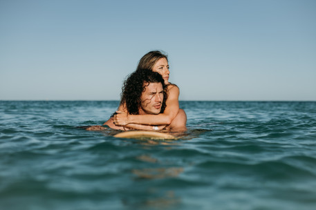 a fit healthy couple on a surf board