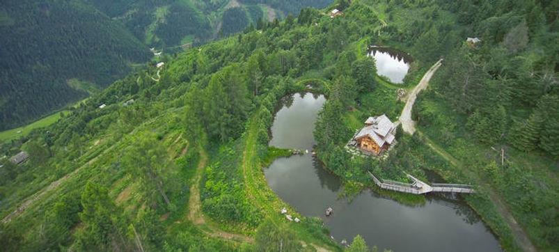photo aérienne de la ferme de Sepp Holzer en Autriche. Krameterhof une ferme au milieu des montagnes Autrichiennes
