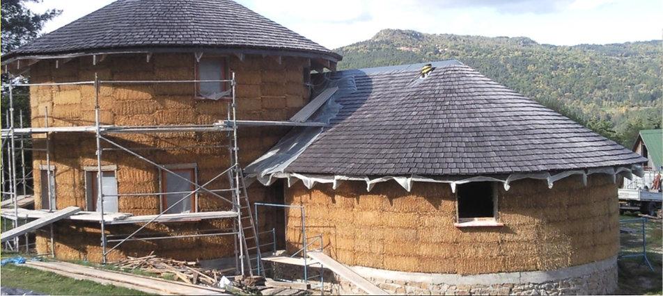 photo d'une maison en paille en construction avec un échafaudage et deux grandes toitures en ardoise avec une montagne au second plan et faisant le lien vers le site internet NaturelHome
