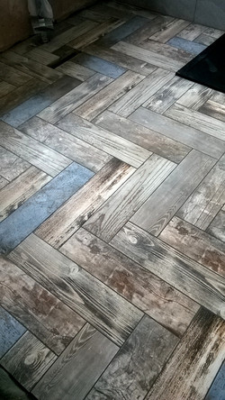 Herringbone wooden plank effect tiled foor