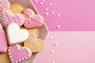 Plate with decorated heart shaped cookies and candy confetti on color background, top view