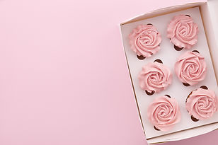 Muffins or cupcakes with flower shaped cream in box on pink background, top view.jpg