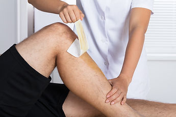 Close-up Of A Therapist Waxing Man's Leg