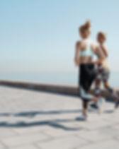 Två flickor Jogging med vatten