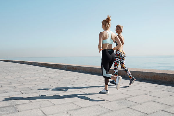 Two Girls Jogging by Water