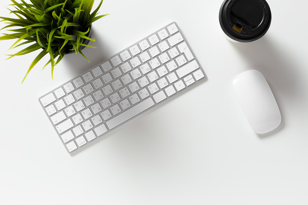 a flatlay of a keyboard, mouse, mug of coffee, and plant