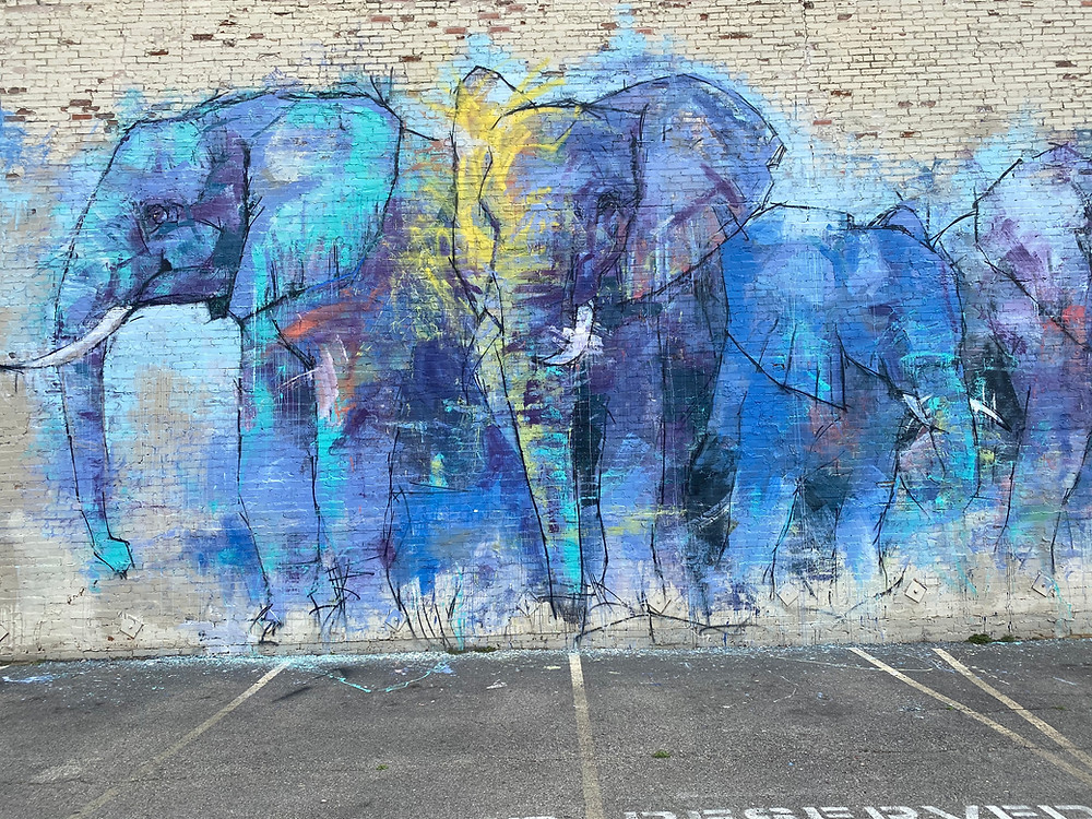 Blue elephants painted on a brick wall.