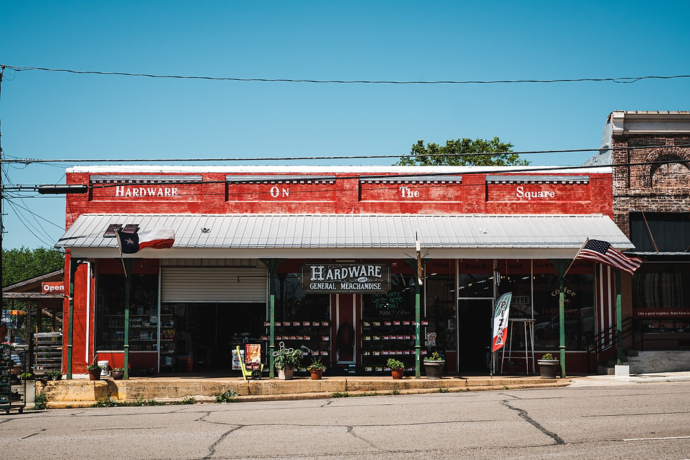 "A red building with vintage lettering ""Hardware, General Merchandise"""