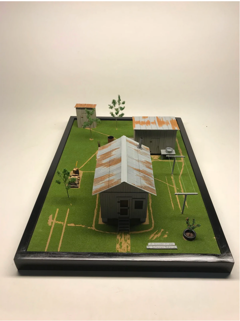 small sculpture of a house in a field