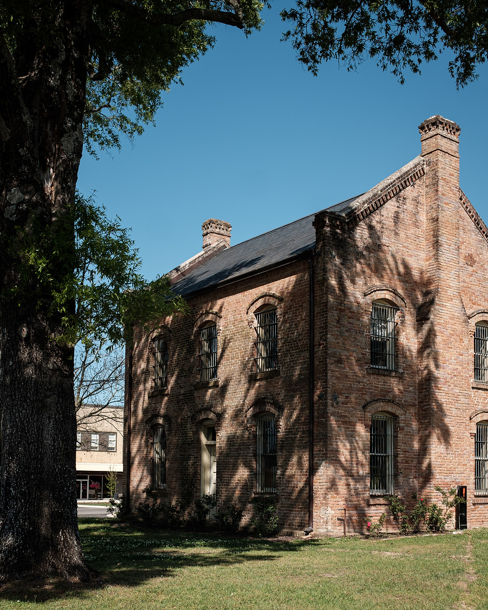 Historic Shelby County Jail in Center Texas. Brick building by trees.