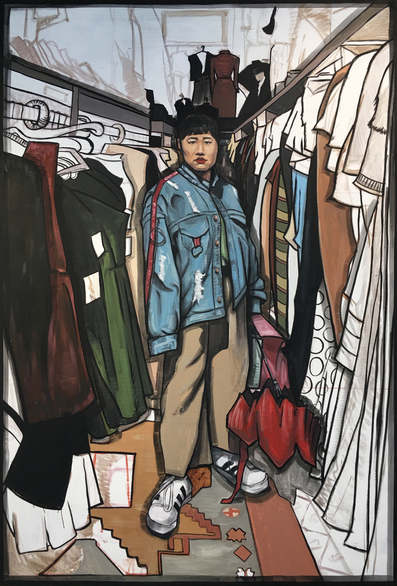 portrait of a young asian woman in a closet with clothes.