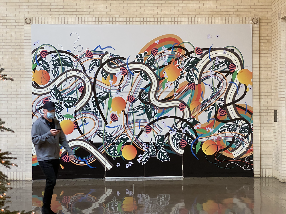 Abstract mural with orange circles and black and white swirls