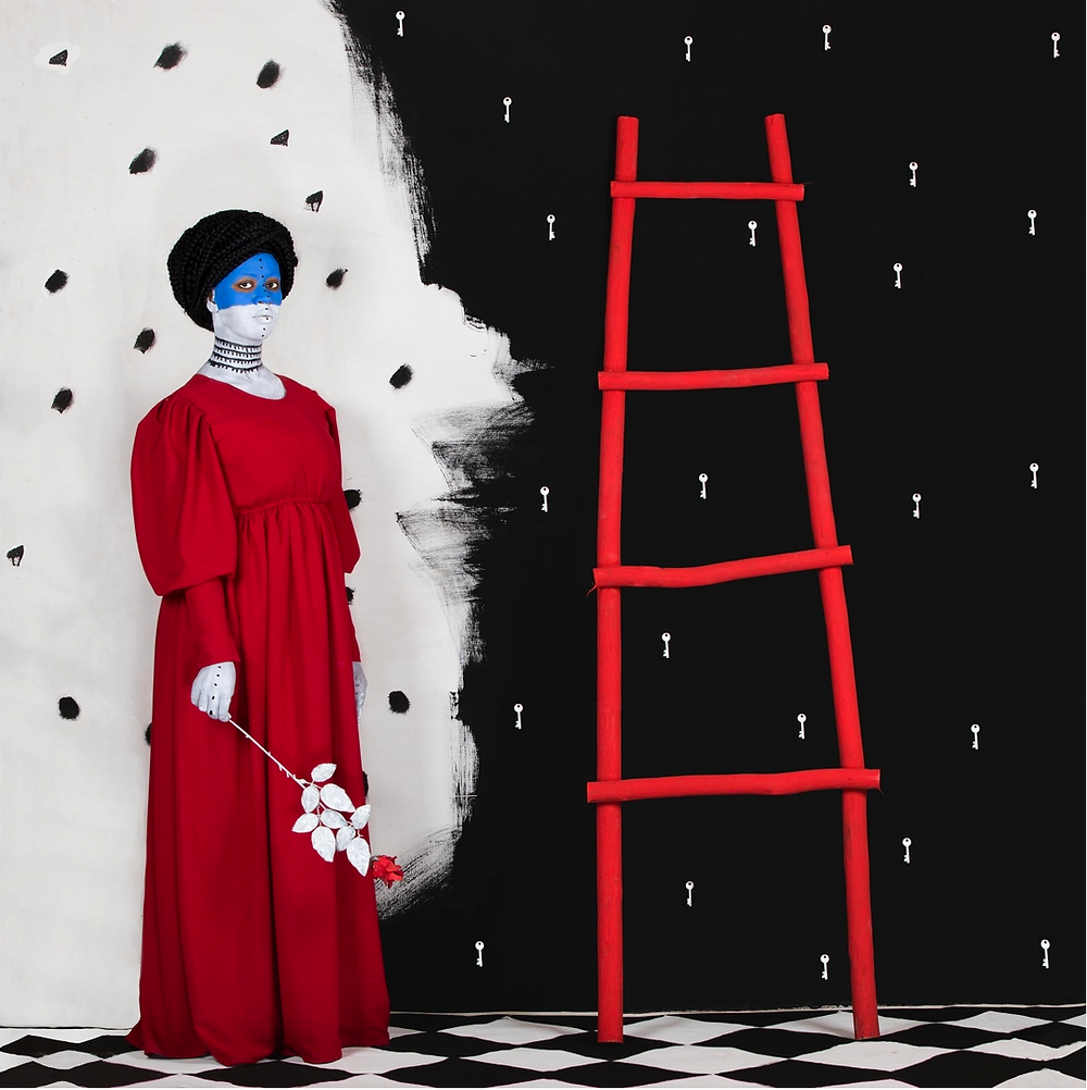 figure of black woman in red dress against red ladder and black and white pattern
